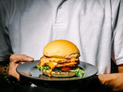 man som håller en hamburgare